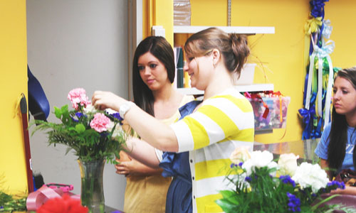 instructor demonstrating floral design technique to a student